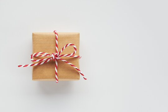 One gift box wrapped in craft paper with striped baker's twine bow on white background. Top view, flat lay, copy space.