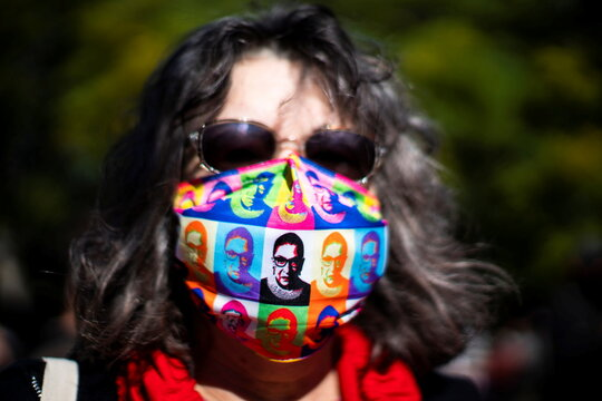 A woman wears a face mask with images of late Justice Ruth Bader Ginsburg as people take part in the 2020 Women's March at Washington Square park in Manhattan, New York