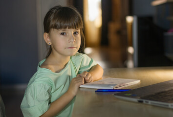 Distance learning education. Cute girl learn english language online with laptop at home. Little girl looks at the camera