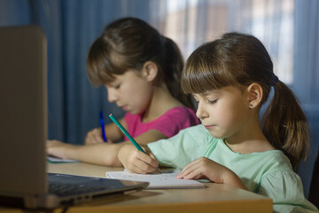 Distance online education. Two schoolgirls study at home and write homework