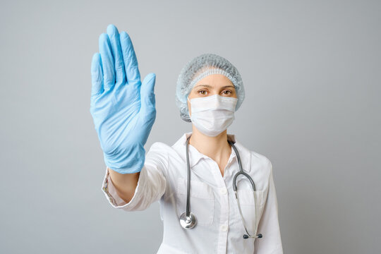Doctor wearing medical face mask and disposable gloves showing stop gesture