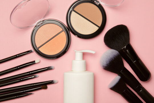 powdery blush, container with an applicator and makeup brushes on a pink background. Cosmetic makeup set
