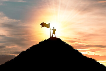 Business achievement objective  target and successful  concept , Silhouette Man standing and holding flag on top of mountain with cloud sky and sunlight. Wall mural