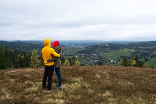 Couple in yellow and red jackets look at the mountains.