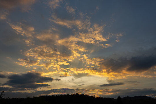 Beautiful sunset with beautiful clouds over the coniferous forest.