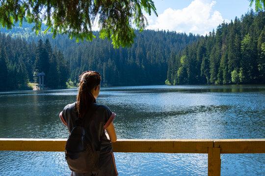 Girl looks at a beautiful mountain lake. Synevyr. Ukraine.