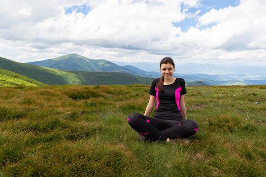 Beautiful girl sits in a meadow among beautiful mountains.