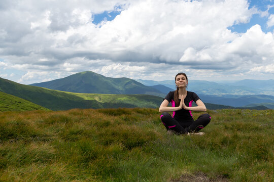 A beautiful girl sits in a meadow with her hands folded in front of her, among the beautiful mountains.