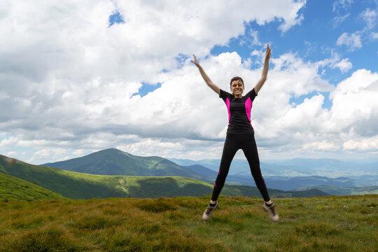 Beautiful girl in a jump, among the beautiful mountains.