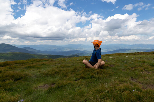 Guy looks at the beautiful mountains, sitting in the meadow.