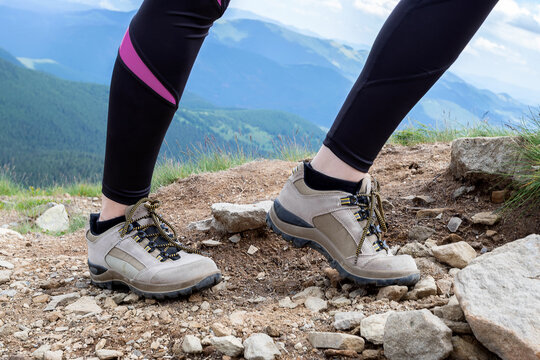 Girl in trekking sneakers on mountain stones. Close-up.