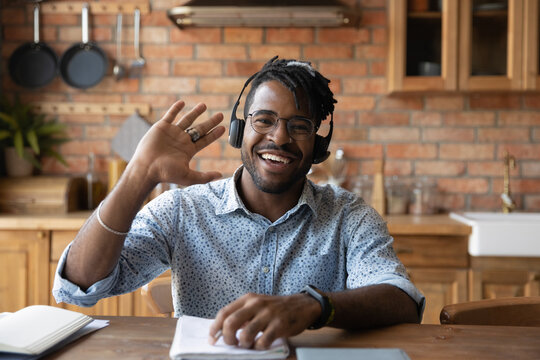 Portrait of smiling African American male blogger in headphones sit at home kitchen office talk on video call. Happy biracial man teacher speaker wave greet have webcam conference or record webinar.
