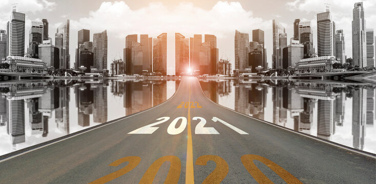 The number 2021 symbol represents the new year on the road heading to the city with beautiful skyscrapers background, New Year's and business target concepts.