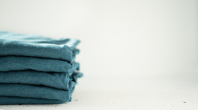 A stack of t-shirts of the same color on a light background. The minimalistic concept. Space for text.