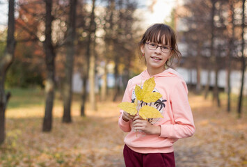 Adorable girl smiles. The teenager holds an armful of leaves at the autumn park.