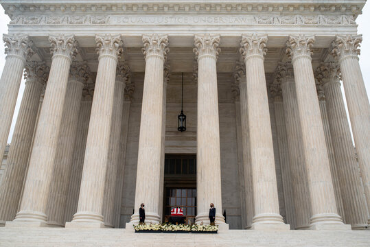 Washington, DC, USA / 9/24/2020: Justice Ruth Bader Ginsburg's casket draped in an American flag on the steps of the Supreme Court.