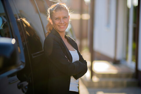 Beautiful woman real estate agent in suit and black car