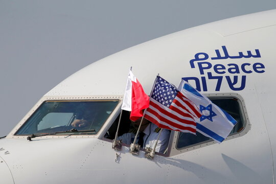 Bahraini, Israeli and U.S. flags are seen on El Al's airliner carrying an Israeli delegation accompanied by the U.S. treasury secretary as it lands in Muharraq