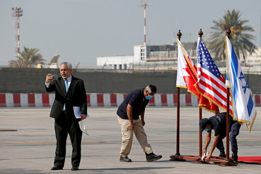 Israeli foreign ministry spokesman Lior Haiat holds a mobile phone as he speaks at Bahrain International Airport, ahead of the arrival of an Israeli delegation accompanied by the U.S. treasury secretary, in Muharraq