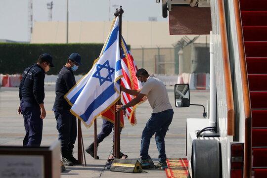 Men adjust Israeli and U.S. flags at Bahrain International Airport ahead of the arrival of an Israeli delegation accompanied by the U.S. treasury secretary, in Muharraq