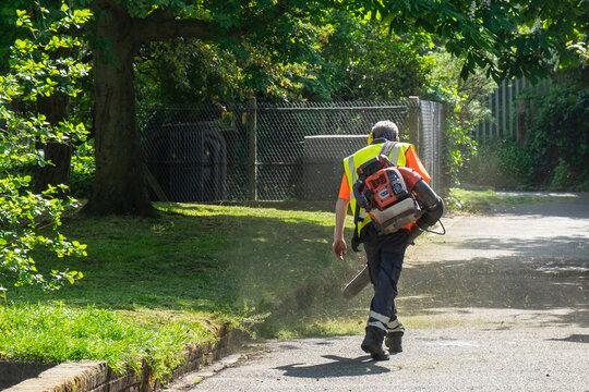 A landscape gardener using a leaf blower to blow away freshly cut grass
