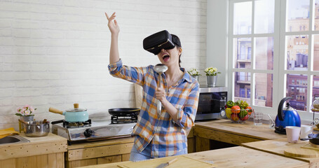 Attractive young funny asian japanese woman in virtual reality headset dancing and singing with ladle while cooking in kitchen at home. beautiful lady wearing vr goggles and enjoying leisure time.