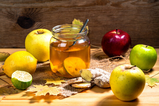 Cold homemade energy drink switchel in a mason jar next to apples, ginger and lemon on a wooden table