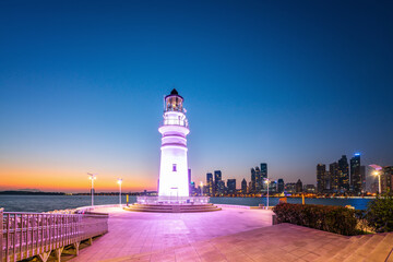 White lighthouse and urban architecture landscape night view
