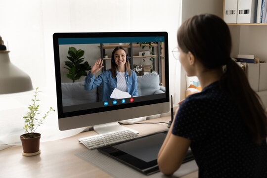 Rear view businesswoman making video call to colleague at home, overjoyed woman waving hand on computer screen, greeting partner, students studying together, working on project online together