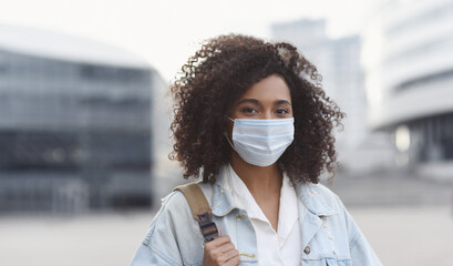 Young woman wearing protective face mask in a city, Masked african teenage student girl on a city...
