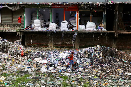 A man collects waste materials including plastics from the waste thrown by local garment companies in Dhaka