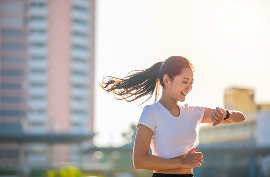 Asian women is watching the sport watch or smart watch for jogging on city