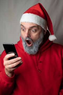Santa Claus looks at a cell phone with his mouth wide open
