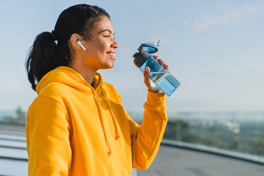 Portrait of a 20s mixed race female runner being thirsty after work out drinking water and wearing yellow hoodie and earphones