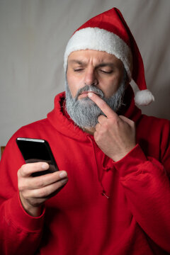 Santa Claus looks at his cell phone suspiciously
