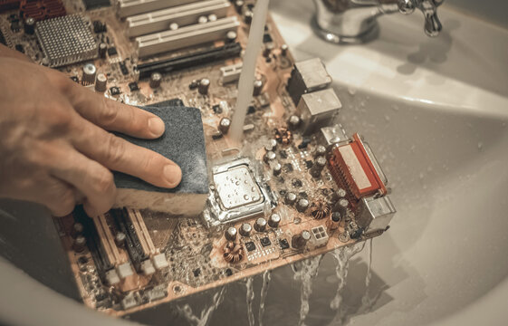 Washing the motherboard from the computer in the sink