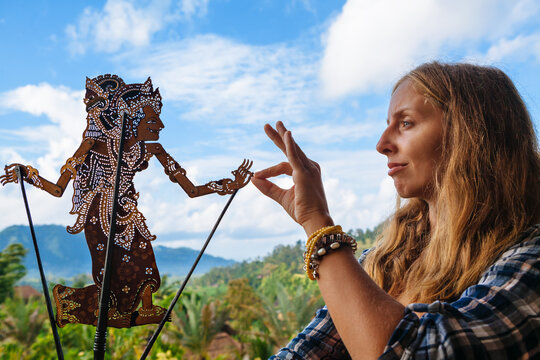Woman holds in hand old traditional shadow puppet of Bali Island - Wayang Kulit. Culture, religion, Arts festivals of Balinese and Indonesian people. Travel background