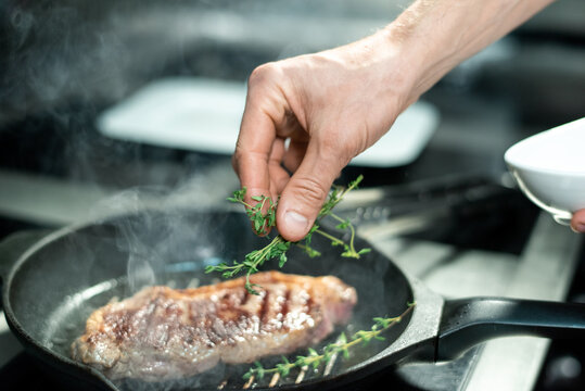 Hand of chef putting green aromatic herbs on roasted piece of beef on frying pan