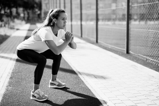 Motivated woman doing deep squats on fresh air