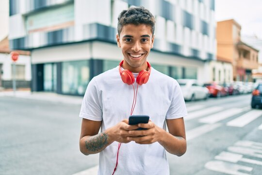 Young latin man smiling happy using smartphone and headphones at the city.