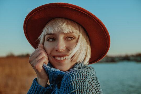 Happy smiling blonde girl wearing orange hat, blue knitted turtleneck sweater, posing outdoors. Close up portrait