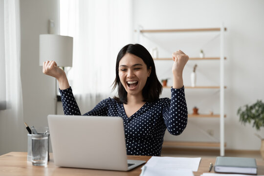 Excited young Vietnamese woman sit at desk at home office triumph reading good unexpected news or email on laptop. Overjoyed asian female look at computer screen feel euphoric win lottery online.