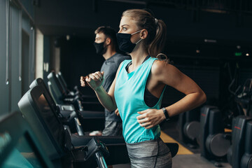 Young fit woman and man running on treadmill in modern fitness gym. They keeping distance and...