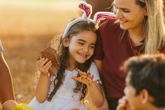 Latin family celebrating Easter. Curly girl wearing bunny ears and eating delicious chocolate egg