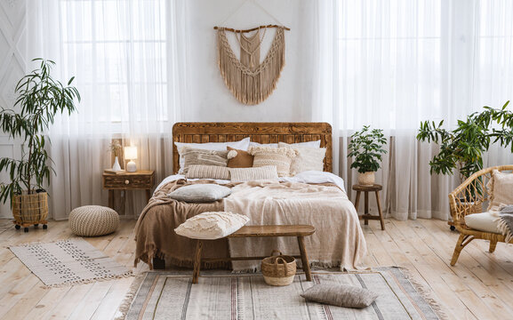 Rustic home design with ethnic boho decoration. Bed with pillows, wooden furniture