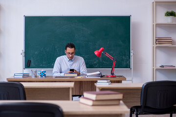 Young male teacher in front of green board