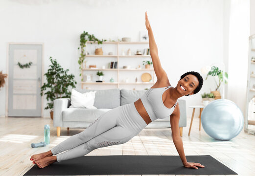 Young African American woman doing strength exercises on mat in living room