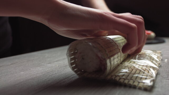 Cropped anonymous cook hands with rolling fresh sushi with bamboo mat while working in authentic Japanese restaurant,Close-up of chef's hands rolling a sushi roll on bamboo mat.Sushi making process