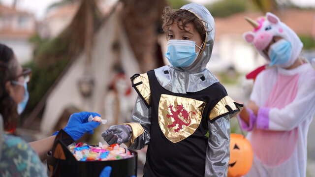 Children wearing costumes and face masks out trick or treating on Halloween 2020. A person hands out candy with gloved hand.