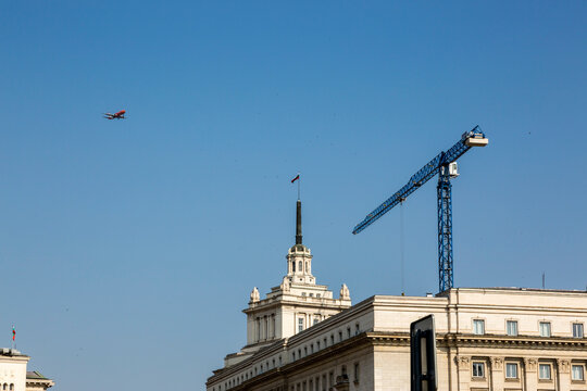 Airplane and crane over the building of Soseta of Ministers of Bulgaria in Sofia